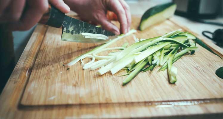 Person schneidet Gemüse auf Schneidebrett aus Holz